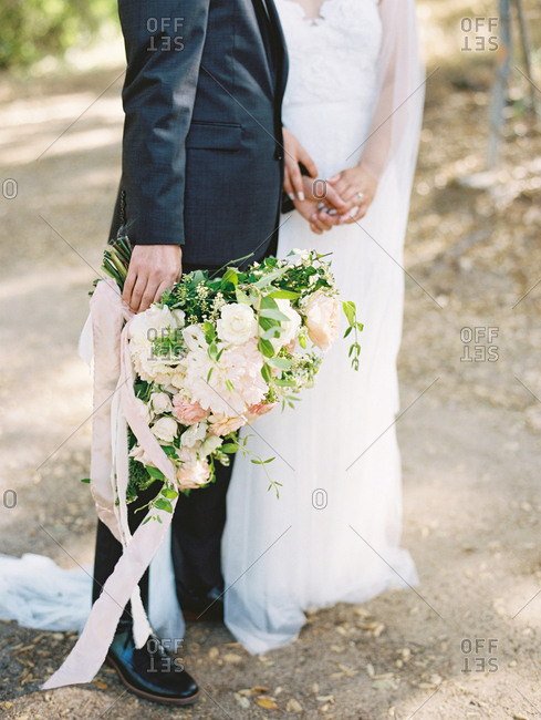 Groom holding bouquet and bride's hand