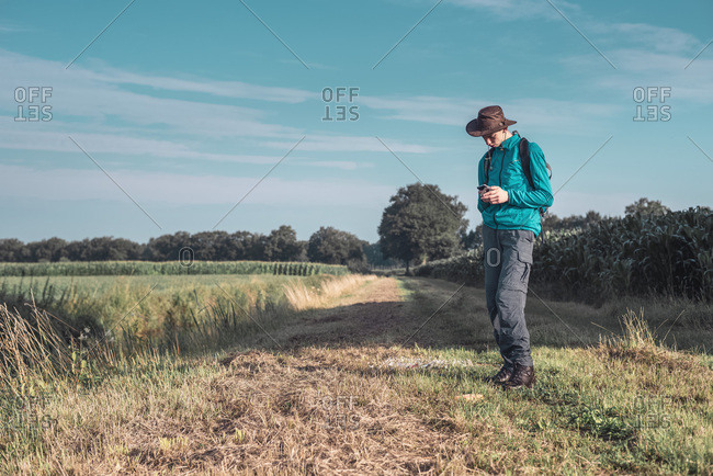 Hiker uses a smartphone in a field