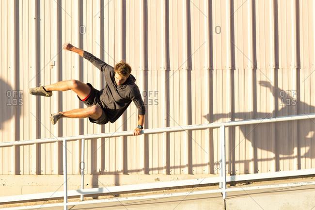 Man in urban city exercising, jumping and running