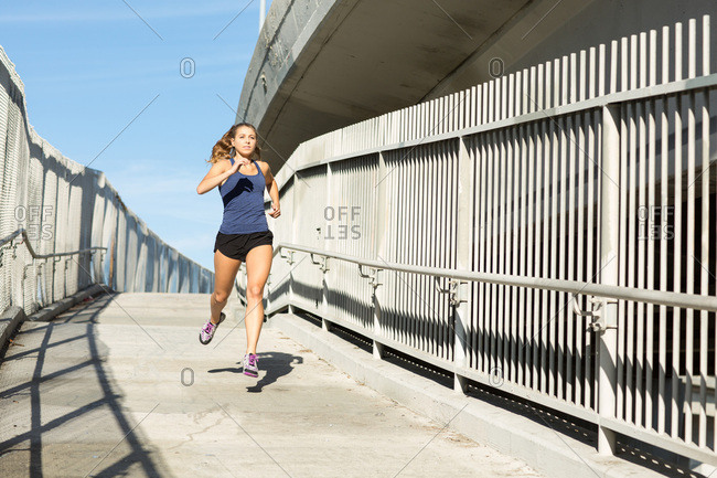 Woman in urban city exercising and running