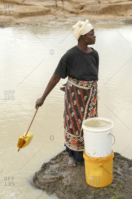 Kenya - July 17, 2009: A Kenyan woman scoops water from a local watering pan into her buckets.