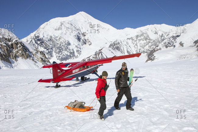 Denali, Alaska, United States - November 29, 2016: Two mountaineers carrying climbing gear in Denali base camp on the Kahiltna glacier