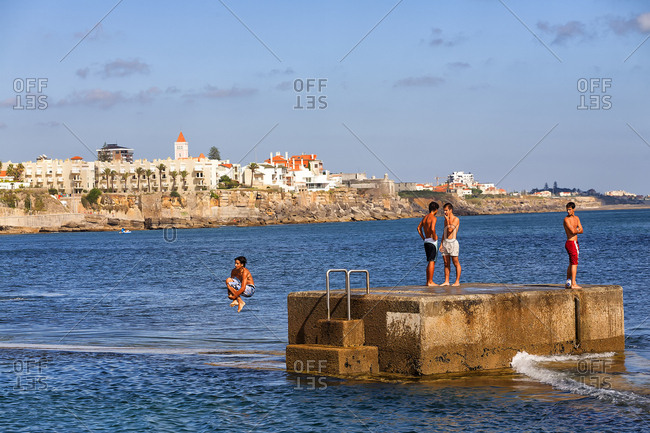 Cascais, Sintra-Cascais, Portugal - August 19, 2000: A wide panorama looking at to sea, of sunbathers and waves at Estoril near Lisbon, Portugal