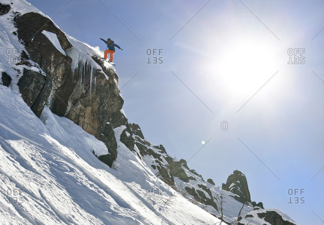 Sans Carlos De Bariloche, Rio Negro, Argentina - July 30, 2012: A Snowboarder Jumping Off A Cliff On A Sunny Day In Argentina