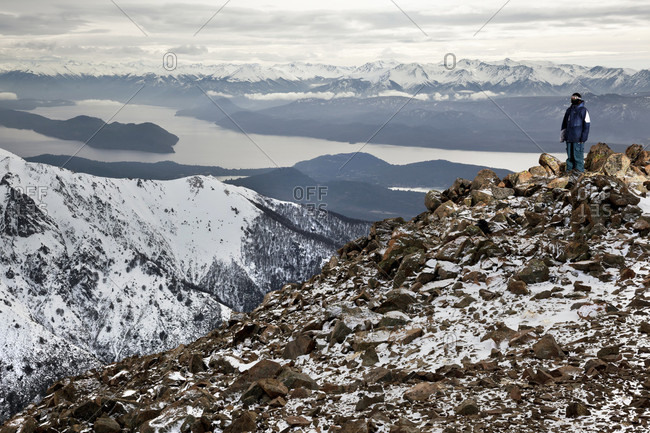 Sans Carlos De Bariloche, Rio Negro, Argentina - August 1, 2012: A Man Stands And Gazes Out At The Andes At The Top Of A Mountain In Argentina