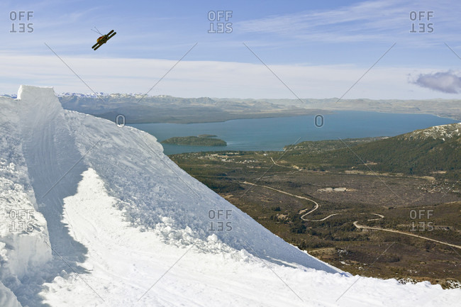 Sans Carlos De Bariloche, Rio Negro, Argentina - August 28, 2013: A Skier Hits A Jump And Grabs His Skies While Skiing At Cerro Catedral, Argentina