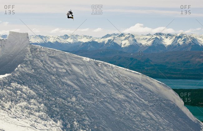Sans Carlos De Bariloche, Rio Negro, Argentina - August 28, 2013: A Snowboarder Hits A Backcountry Jump And Does A Classic Snowboard Trick In The Cerro Catedral, Argentina
