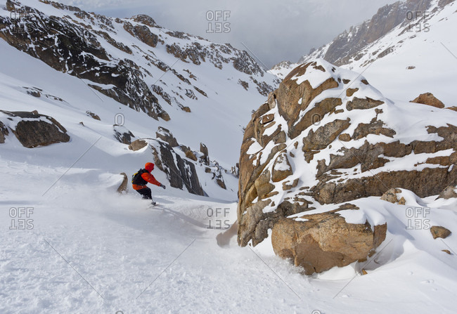 Sans Carlos De Bariloche, Rio Negro, Argentina - September 1, 2013: A Snowboarder Goes Between Rocks In The Backcountry Of Cerro Catedral, Argentina