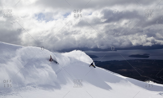 Sans Carlos De Bariloche, Rio Negro, Argentina - August 6, 2014: Two Snowboarders Riding Together And Slash A Windlip During Stormy Day In Argentina