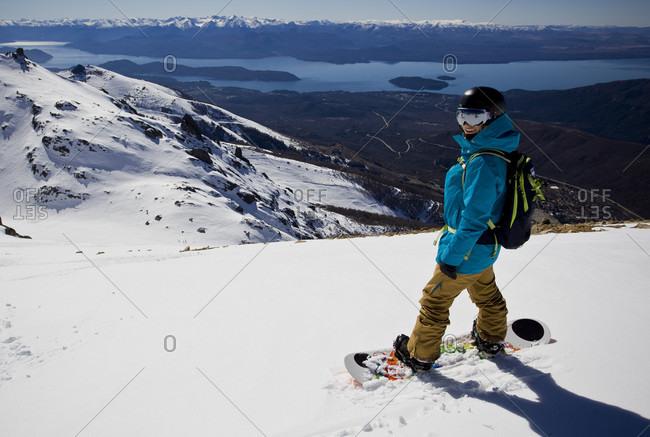 Sans Carlos De Bariloche, Rio Negro, Argentina - August 25, 2014: Smiling Professional Snowboarder On Snowboard At Snowy Landscape