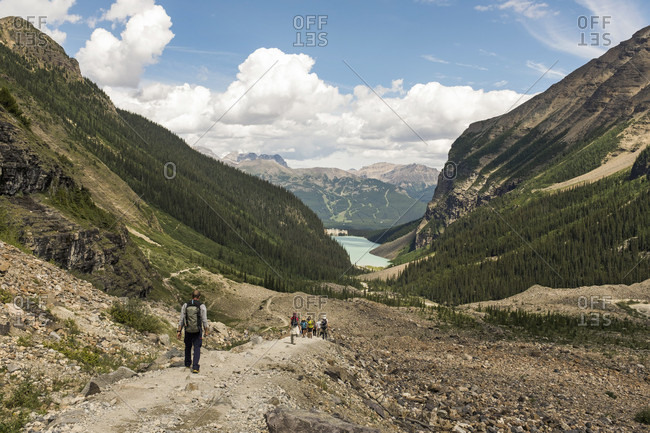 Lake Louise, Alberta, Canada - July 28, 2016: Hikers walk down a trail in Lake Louise in Banff National Park, Canada.