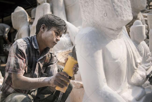 Amarapura, Mandalay, Myanmar - March 13, 2015: A local man carving a marble Buddha statue using an angle grinder, Amarapura, near Mandalay, Myanmar.