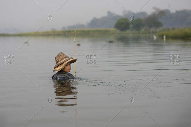 Amarapura, Mandalay, Myanmar - March 12, 2015: A woman fishing in a traditional style at the Taungthaman Lake, Amarapura, Myanmar.