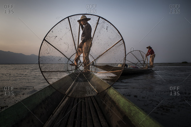 Inle Lake, Nyaungshwe, Myanmar - March 25, 2015: Two fishermen in their boats at the Inle Lake, Nyaungshwe, Myanmar.