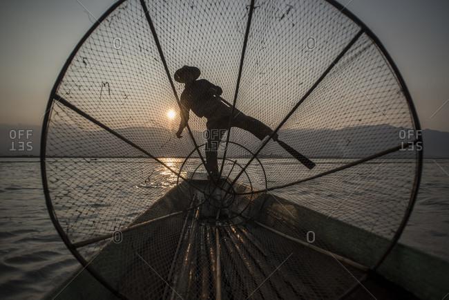 Inle Lake, Nyaungshwe, Myanmar - March 25, 2015: Silhouette of a Inle Lake Fisherman at work, Nyaungshwe, Shan State, Myanmar.