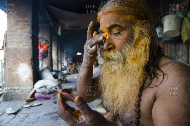 Pashupatinath Temple, Kathmandu, Nepal - March 29, 2012: A Shaivite Hindu Holy Man Applies Symbolic Coloring To His Face At Pashupatinath Temple, Nepal