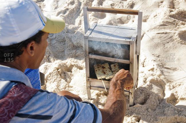 Rio de Janeiro, Rio de Janeiro, Brazil - June 14, 2014: Man cooks salty cheese on a stick on a mini grill on the beach