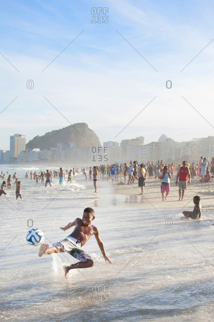 Rio de Janeiro, Rio de Janeiro, Brazil - June 14, 2014: A little boy kicks a soccer ball in the surf of Copacabana beach