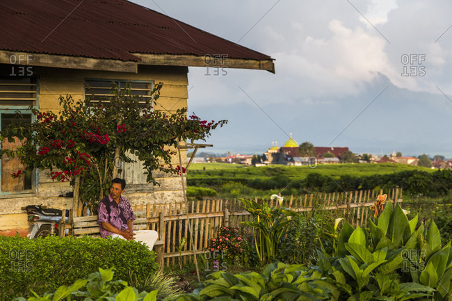 Kerinci Valley, Sumatra, Indonesia - February 21, 2015: A man sits on the front porch of his home in the tea fields in Kerinci Valley of Sumatra, Indonesia.