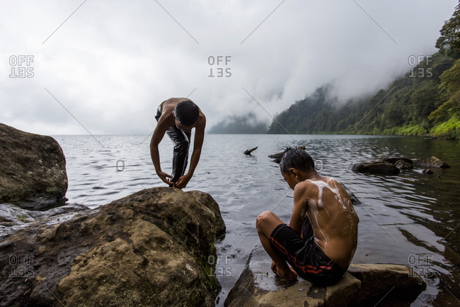 Kerinci Valley, Sumatra, Indonesia - February 21, 2015: Two boys, their bodies covered in suds, bathe with soap while standing at the edge of a large, cloud-covered lake surrounded by mountains. Kerinci Valley, Sumatra, Indonesia.
