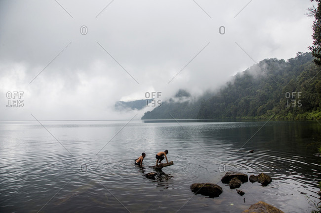 Kerinci Valley, Sumatra, Indonesia - February 21, 2015: Two young boys play and swim around a half-submerged log in a large, cloud-covered lake surrounded by mountains. Kerinci Valley, Sumatra, Indonesia