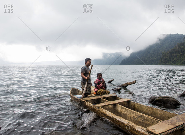 Kerinci Valley, Sumatra, Indonesia - February 22, 2015: A young man stands and old man sits in the back of a hand-carved dugout canoe on a lake shrouded in clouds. Kerinci Valley, Sumatra, Indonesia