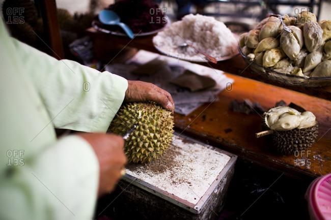 Kerinci Valley, Sumatra, Indonesia - February 27, 2015: A street vendor cuts open a fresh, local fruit at a street market in Kerinci Valley, Sumatra, Indonesia.