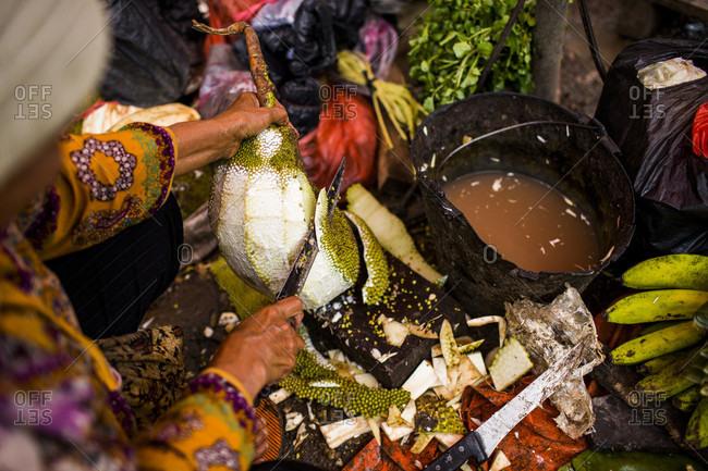 Kerinci Valley, Sumatra, Indonesia - February 27, 2015: A woman prepares fresh vegetables at a local market in Kerinci Valley, Sumatra, Indonesia.