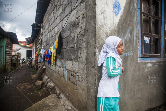 Kerinci Valley, Sumatra, Indonesia - February 28, 2015: A young Muslim girl stands on the corner of the street in a small town in Sumatra, Indonesia.