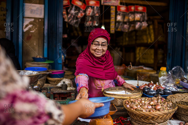 Kerinci Valley, Sumatra, Indonesia - February 27, 2015: An elderly woman works at a street stand in a market in a city in Sumatra, Indonesia.