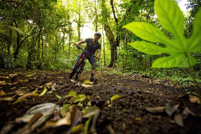 Kintamani, Bali, Indonesia - September 24, 2016: Man Mountain Biking In Tropical Forest Of Bali, Indonesia