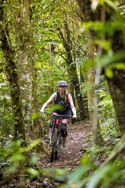 Kintamani, Bali, Indonesia - September 24, 2016: Female Mountain Biker Riding In Forest Trail Of Bali, Indonesia