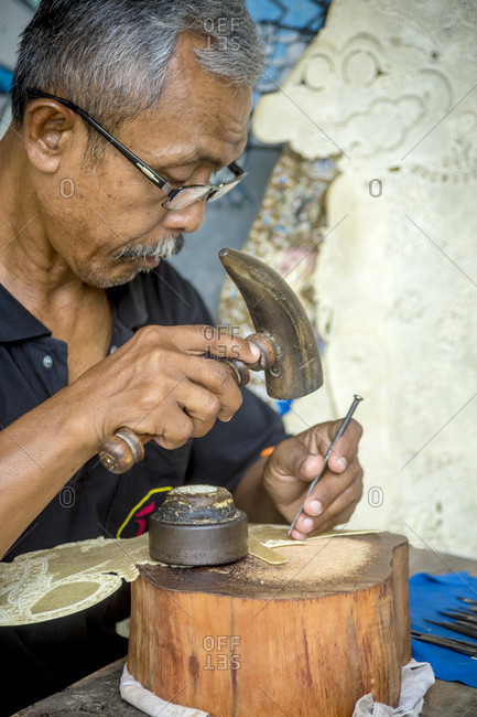 Yogyakarta, Java, Indonesia - October 13, 2016: Man Making Traditional Shadow Puppet With Leather And Hammer In Workshop