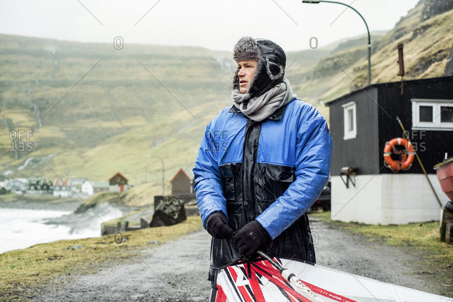 Tjornuvik, Streymoy, Faroe Islands - May 6, 2015: Professional Windsurfer Prepares His Gear For Surfing In The Freezing Water, Faroe Islands