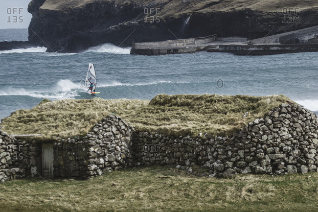 Streymoy, Faroe Islands, Faroe Islands - August 9, 2017: Professional Windsurfer In The Freezing Water Of The Faroe Islands