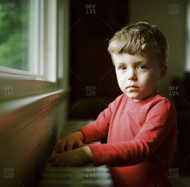 Portrait of a little boy standing by window