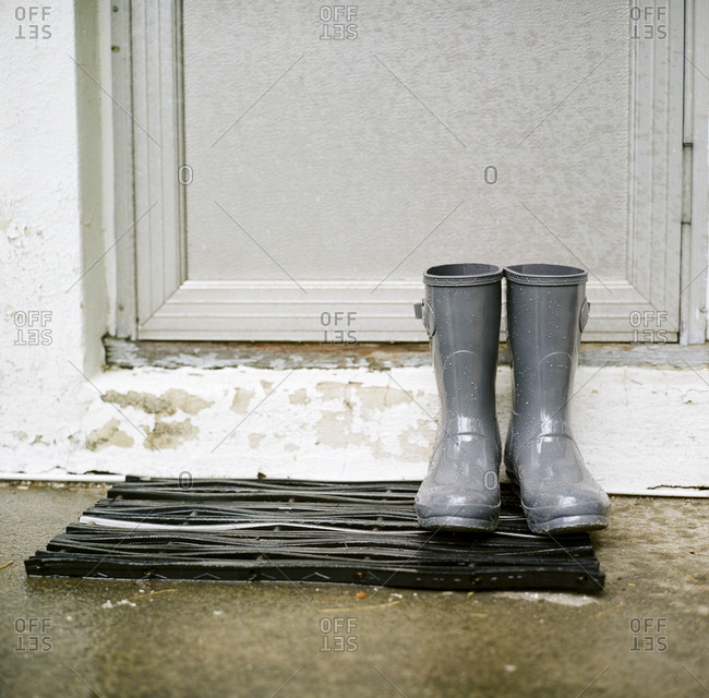 Gray rain boots on a mat by a door