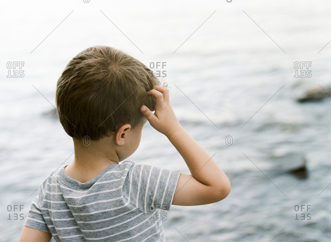 Little boy looking out at water