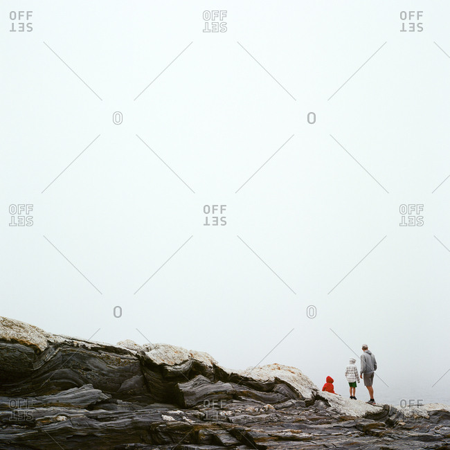 Father and sons standing on rocky cliff overlooking water