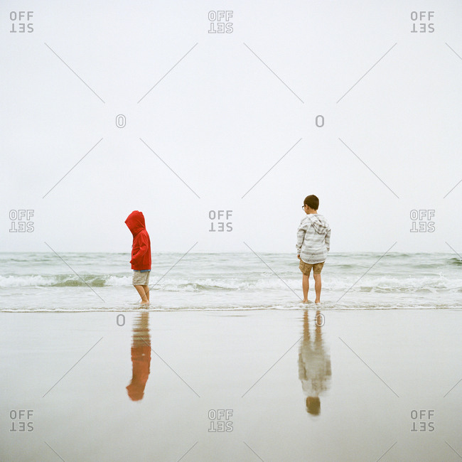 Little boys standing in ocean waves together