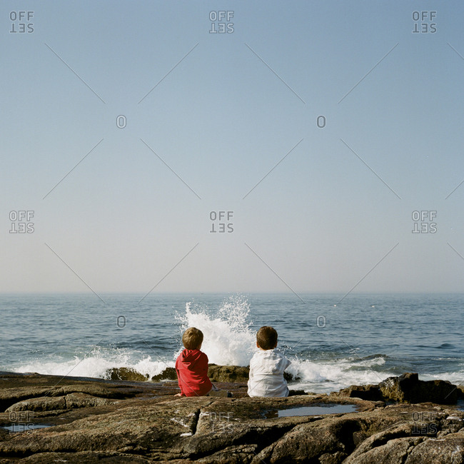 Brothers sitting on rocky shore looking at waves
