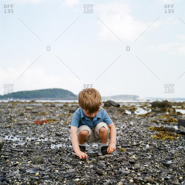 Boy looking at rocks on a beach