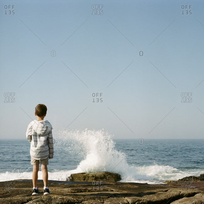 Boy standing on rocky shore looking at waves