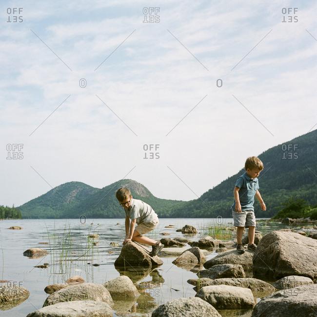 Two boys exploring on rocks by lake