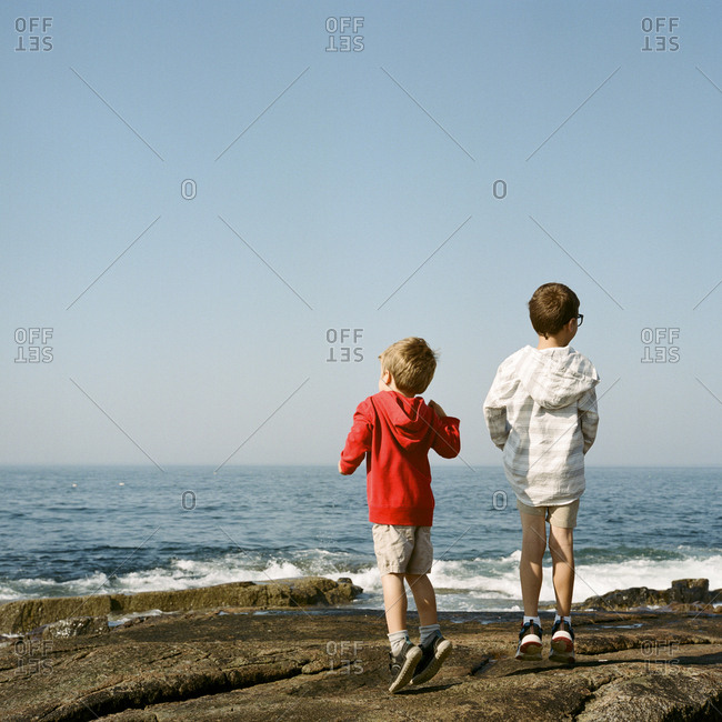 Brothers jumping on rocky shore looking at waves