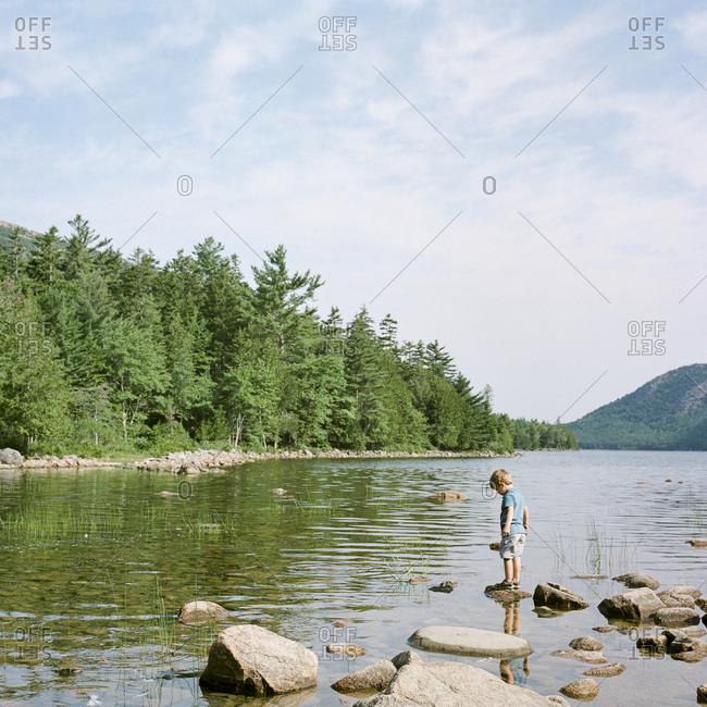 Little boy exploring on rocks by lake