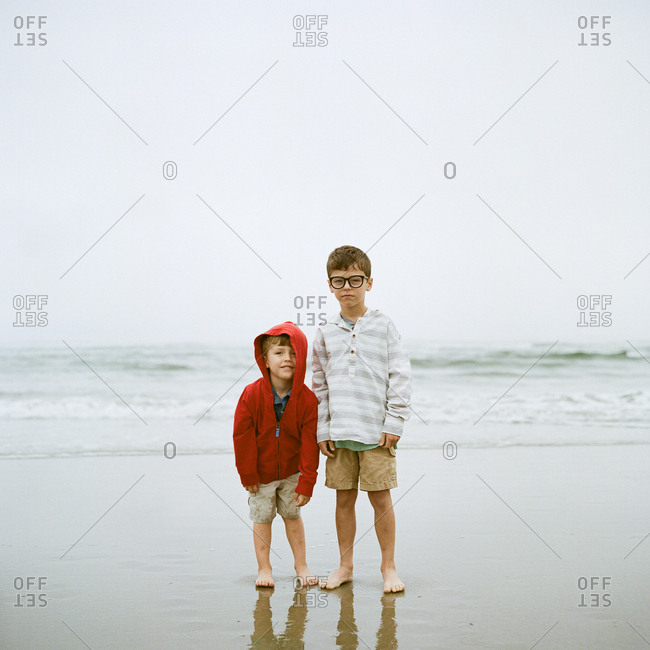 Brothers standing on ocean shore together