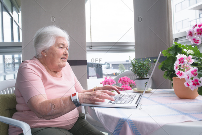 Senior woman using laptop at kitchen table