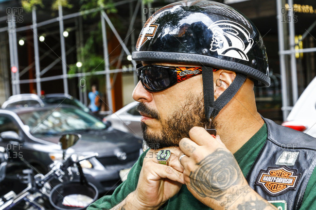 New York City, New York - August 5, 2017: A biker strapping on his helmet