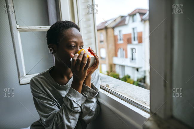 Woman enjoying view from window while drinking coffee